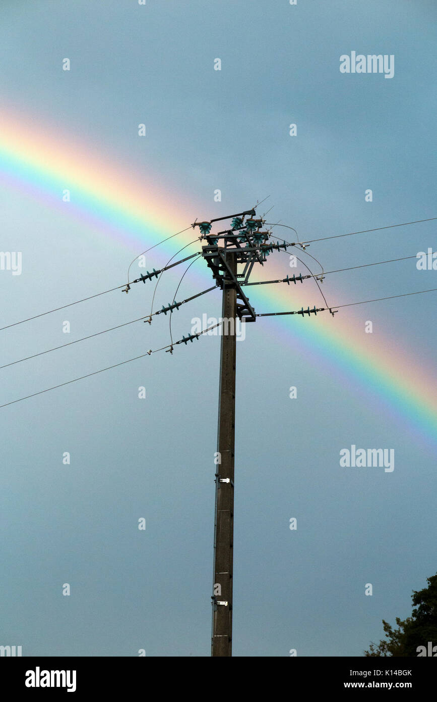 Rainbow behind electricity transmission wires and pylon to the show and signify clean, green, modern, efficient electricity transmission & generation. - Stock Image
