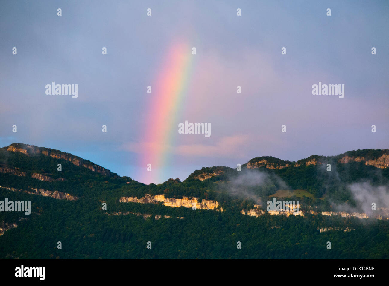 View – with rainbow – across Lac Du Bourget from Conjux to ridge between Col Du Sapenay and La Chambotte & the mountainside below it. Savoy, France - Stock Image
