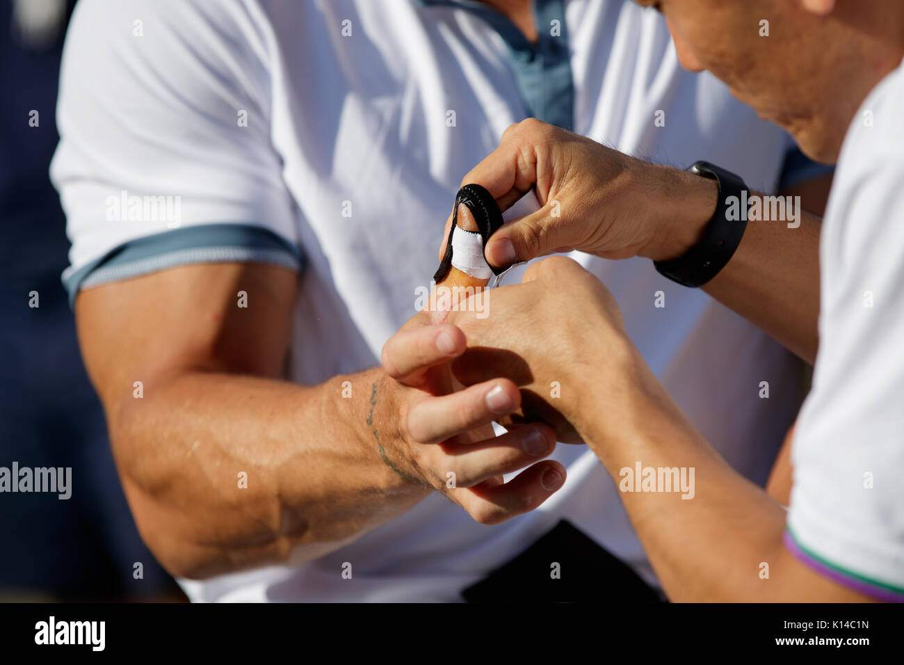 Gustavo Fernandez of Argentina has his thumb attended to by a medic at the Gentlemen's Wheelchair Doubles - Wimbledon Championships 2017 - Stock Image