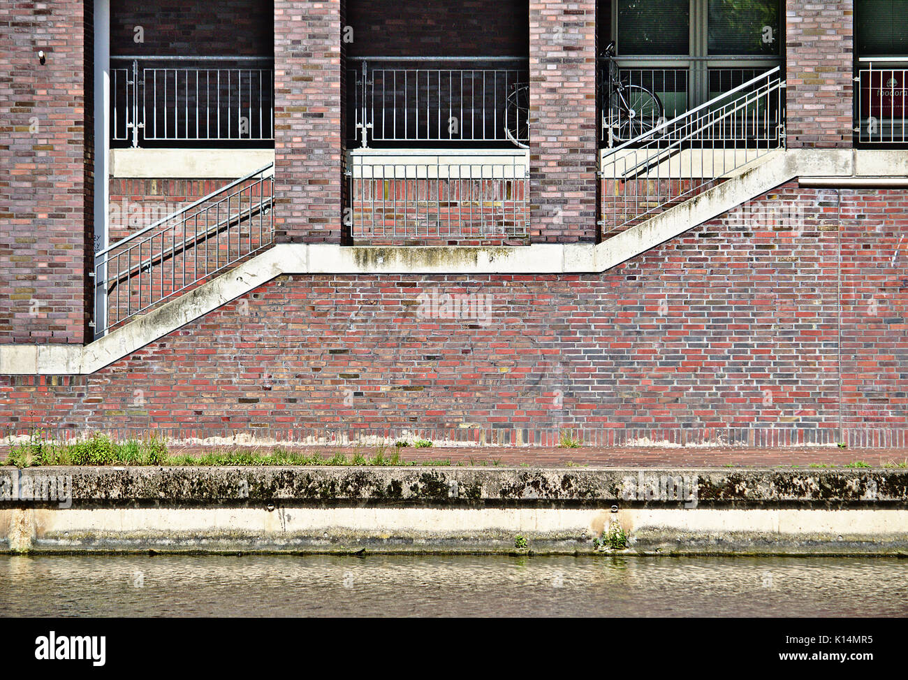 Waterfront building with sidewalk, flight of stairs, red and grey brick wall and brick pillars - Stock Image