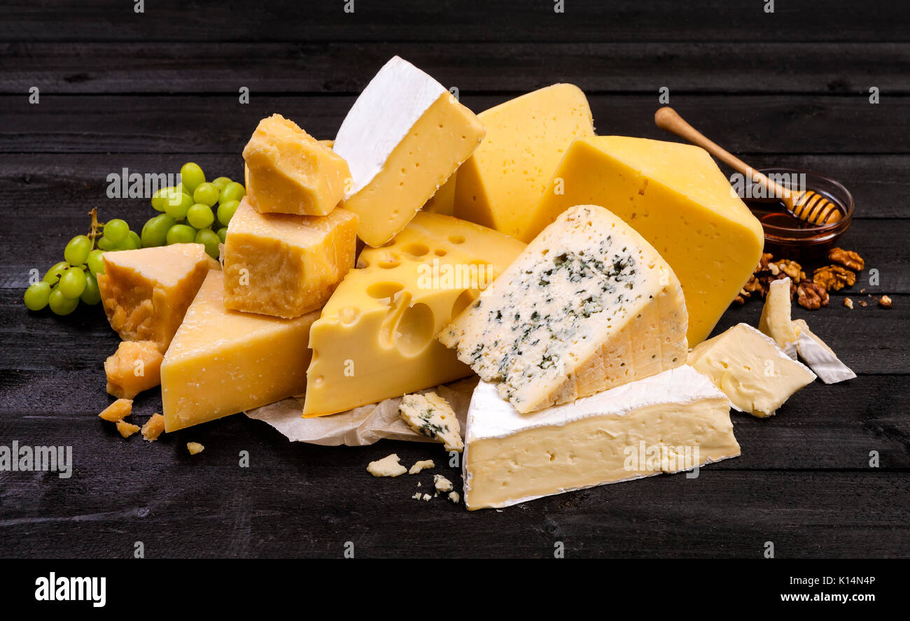 Various types of cheese on black wooden table. - Stock Image