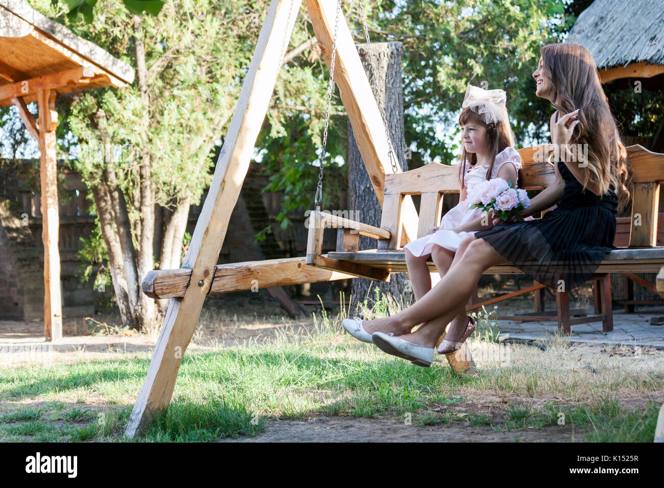 Little girl enjoying with her mother in summer day. They sit on the bench and enjoy a beautiful sunny day. Family time - Stock Image
