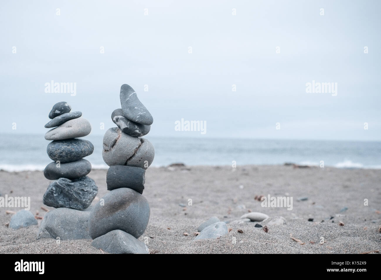 Monochrome, Serene, Blue Stacked rocks on a California beach symbolizing Peace, Balance, Meditation, and Mindfulness Stock Photo