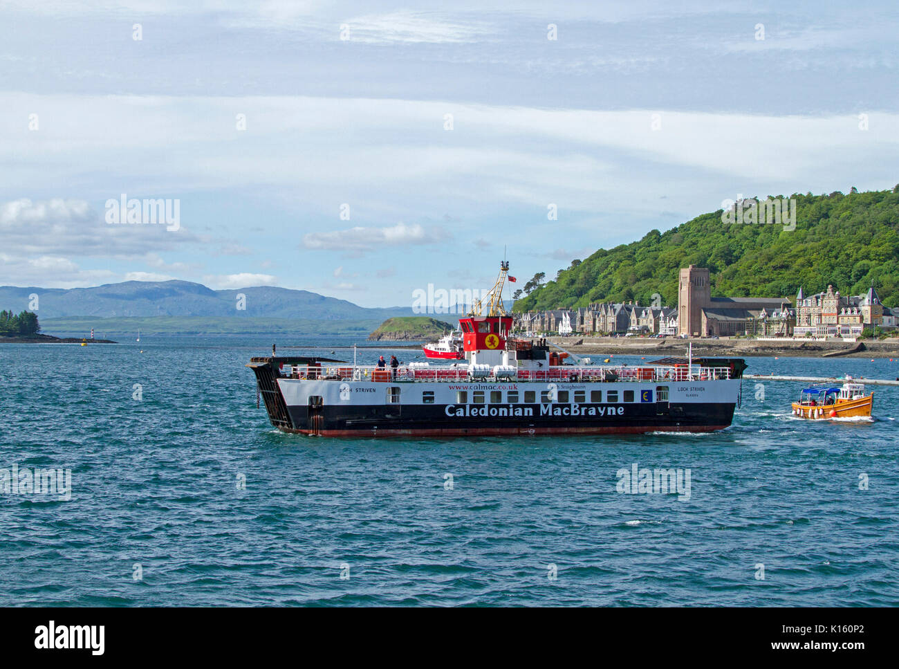Large black and white vehicular and passenger ferry, Caledonian MacBrayne, at Oban harbour, Scotland with buildings Stock Photo