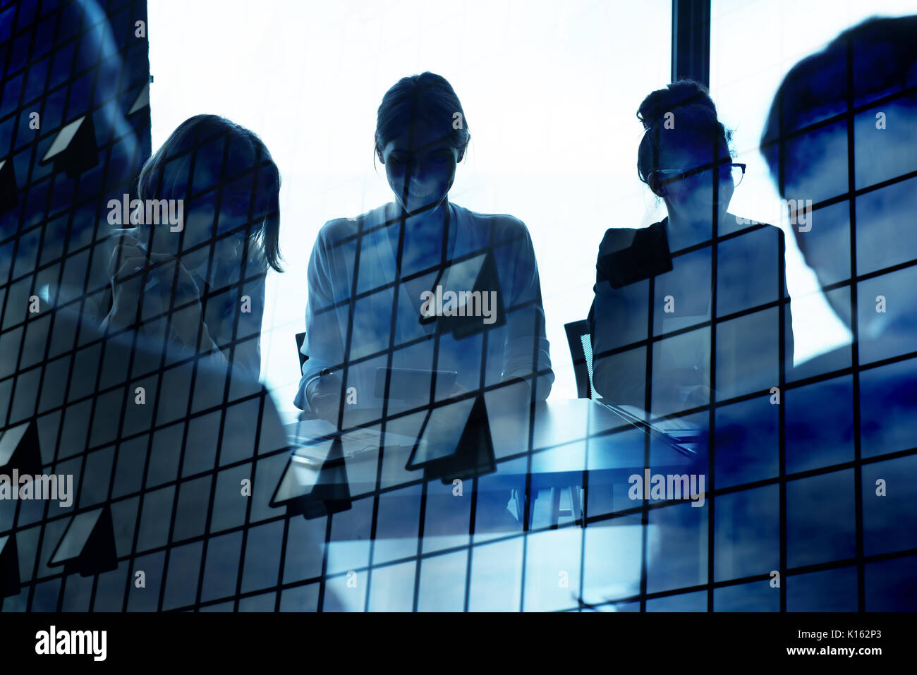 Silhouette of businessperson in office with skyscraper effect. concept of partnership and teamwork - Stock Image