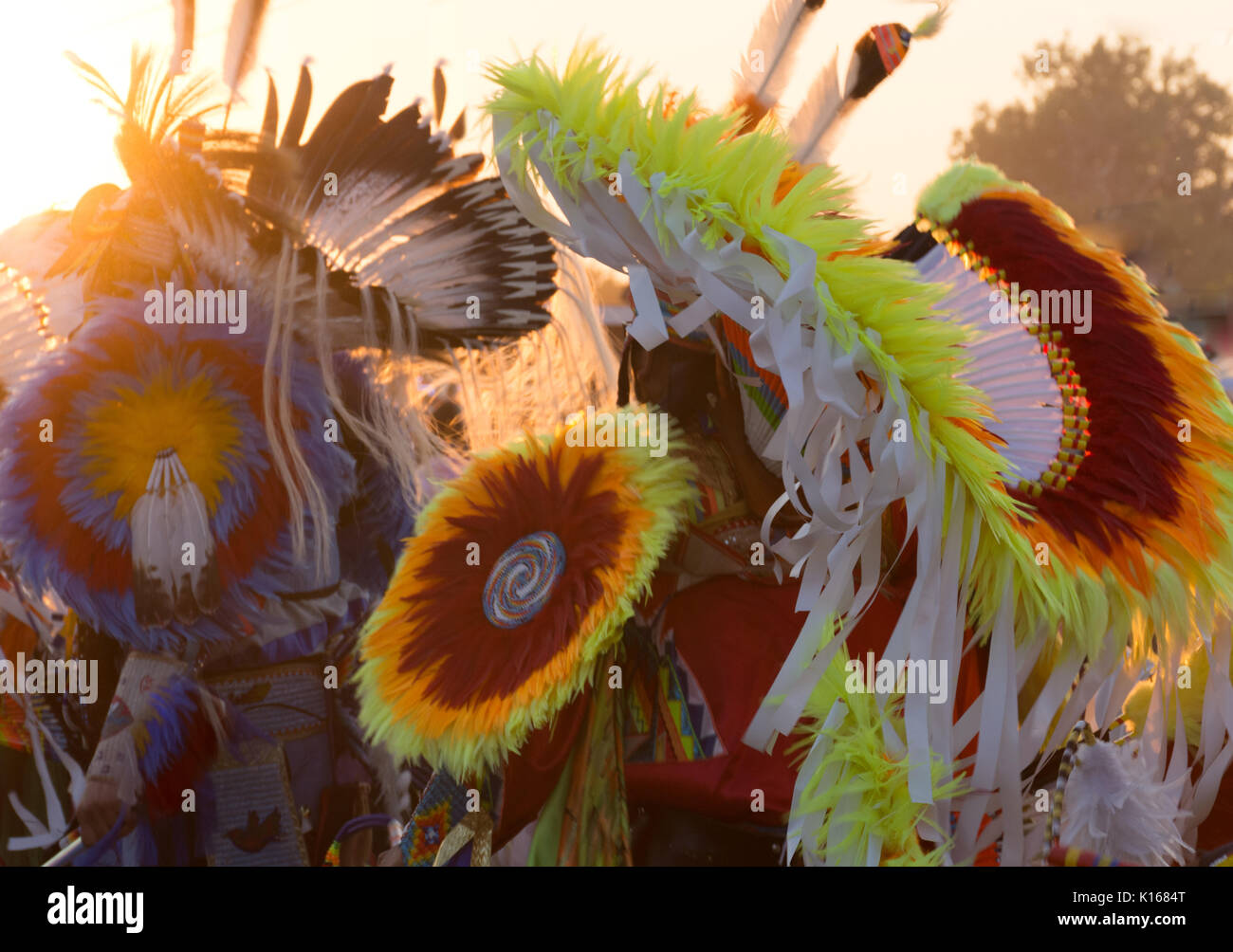Colorful headdresses worn at a Powwow. Feathers, ribbons and beads in red, yellow, orange, blue and white are photographed with shallow depth of field. - Stock Image