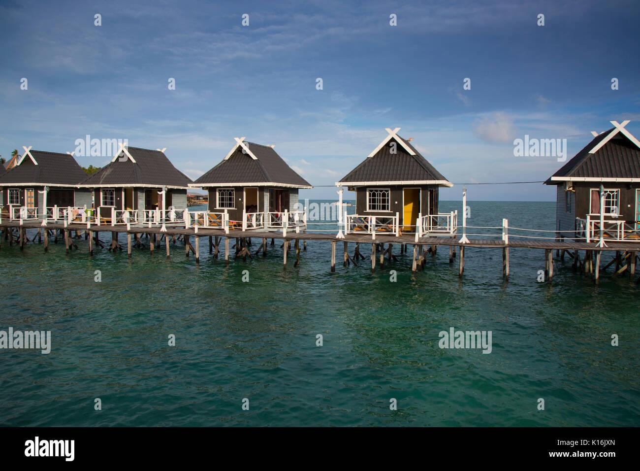Tourist bungalows over the ocean at Billabong Dive Resort, Mabul Island - Stock Image