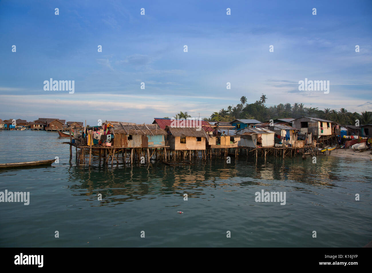 Minimalist dwellings on stilts in poor neighborhood on Mabul Island, Borneo - Stock Image