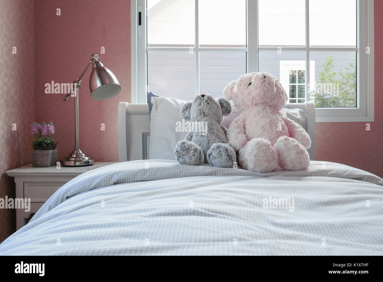 Kids Room With Dolls And Pillows On Bed And Bedside Table Lamp Stock