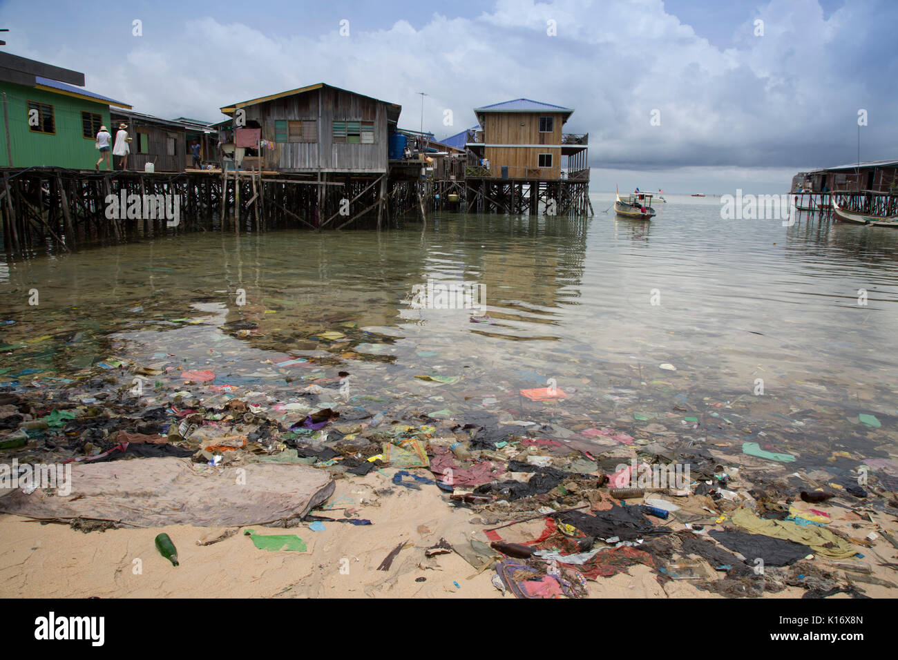 Plastic trash and other garbage make for an ugly beach scene on Mabul Island, Borneo. The wooden buildings on stilts are budget dive resorts - Stock Image