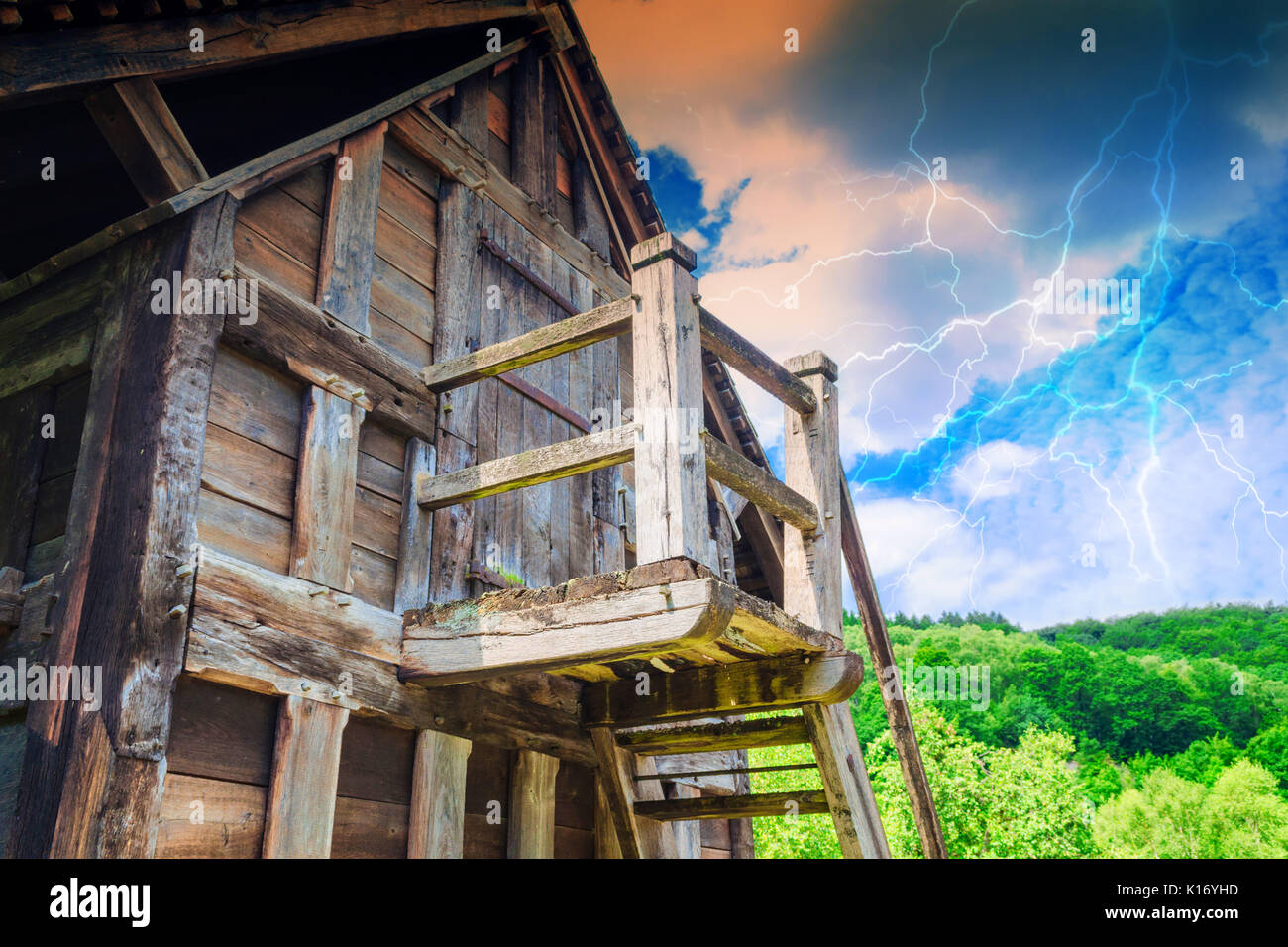 Idyllic Alpine shelter or chalet in summer on a mountain meadow during thunderstorm. Stock Photo