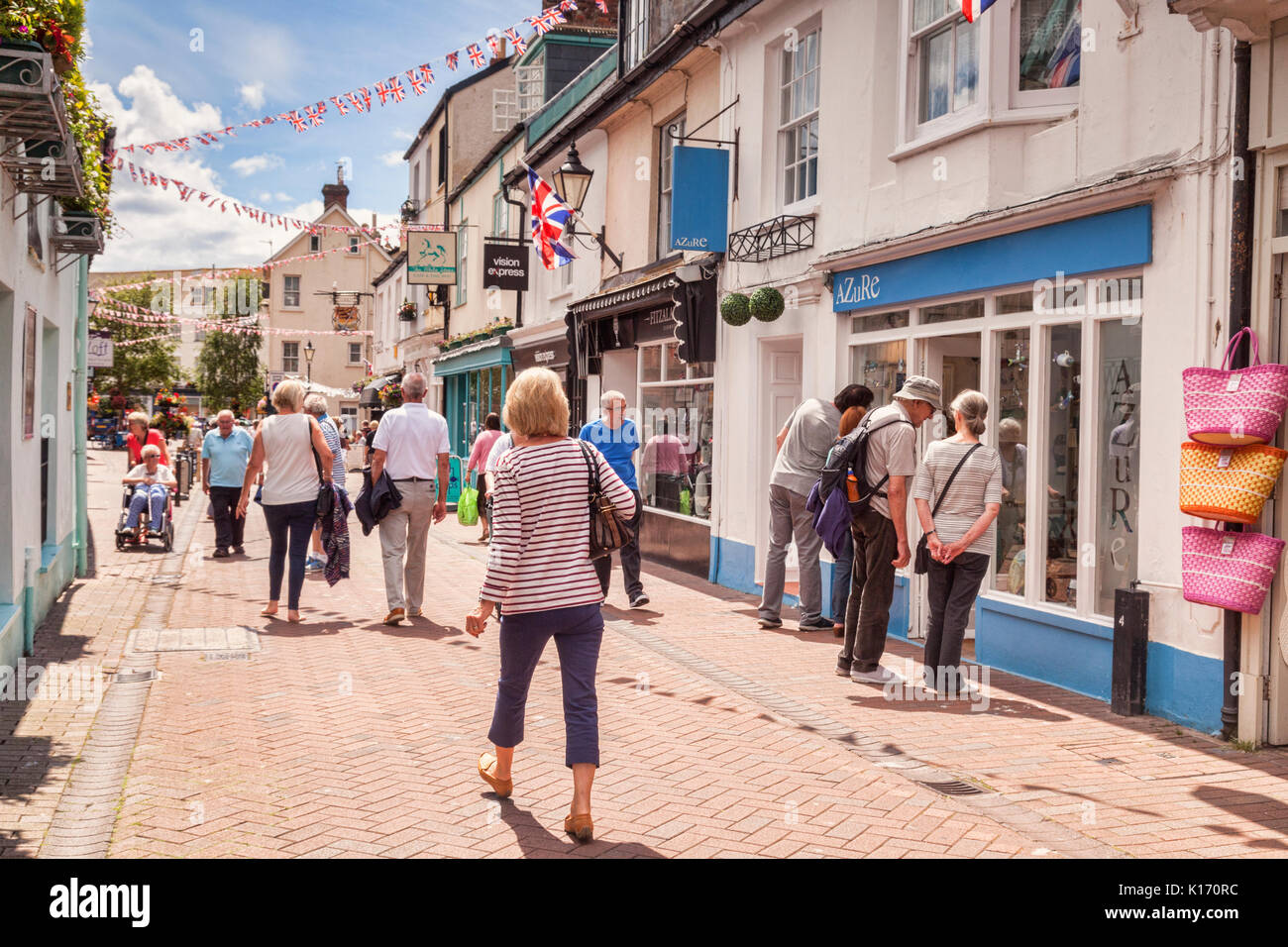 # July 2017: Sidmouth, Dorset, England, UK - People shopping in Old Fore Street on a sunny summer day. Focus on Stock Photo