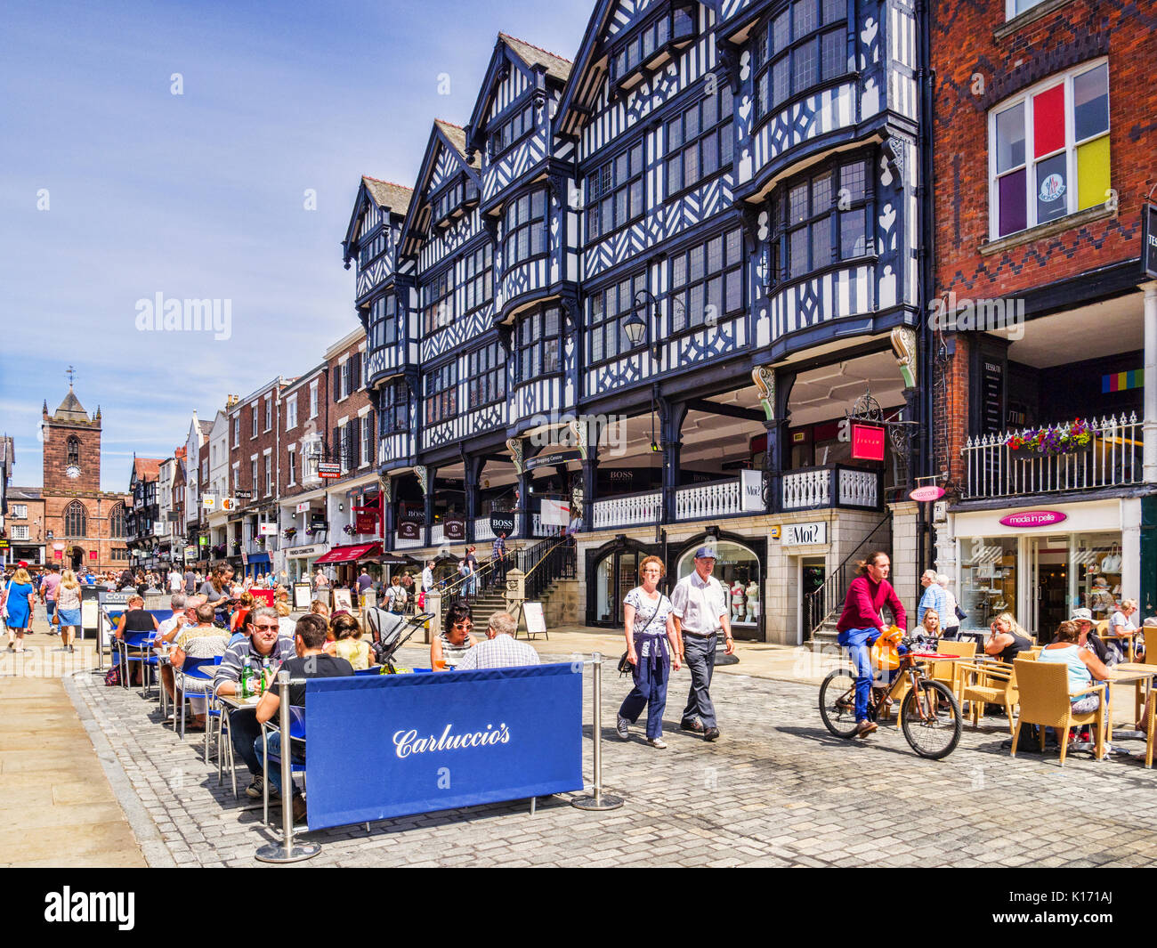 18 July 2017: Chester, Cheshire, England, UK - Half timbered houses in Bridge Street, and Carluccio's restaurant, with people sitting outside in the s Stock Photo