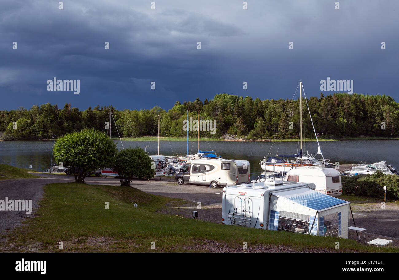 GRISSLEHAMN, SWEDEN ON 25, 2017. View of a marina this side an island. Evening and heavy showers in the background. Editorial. - Stock Image