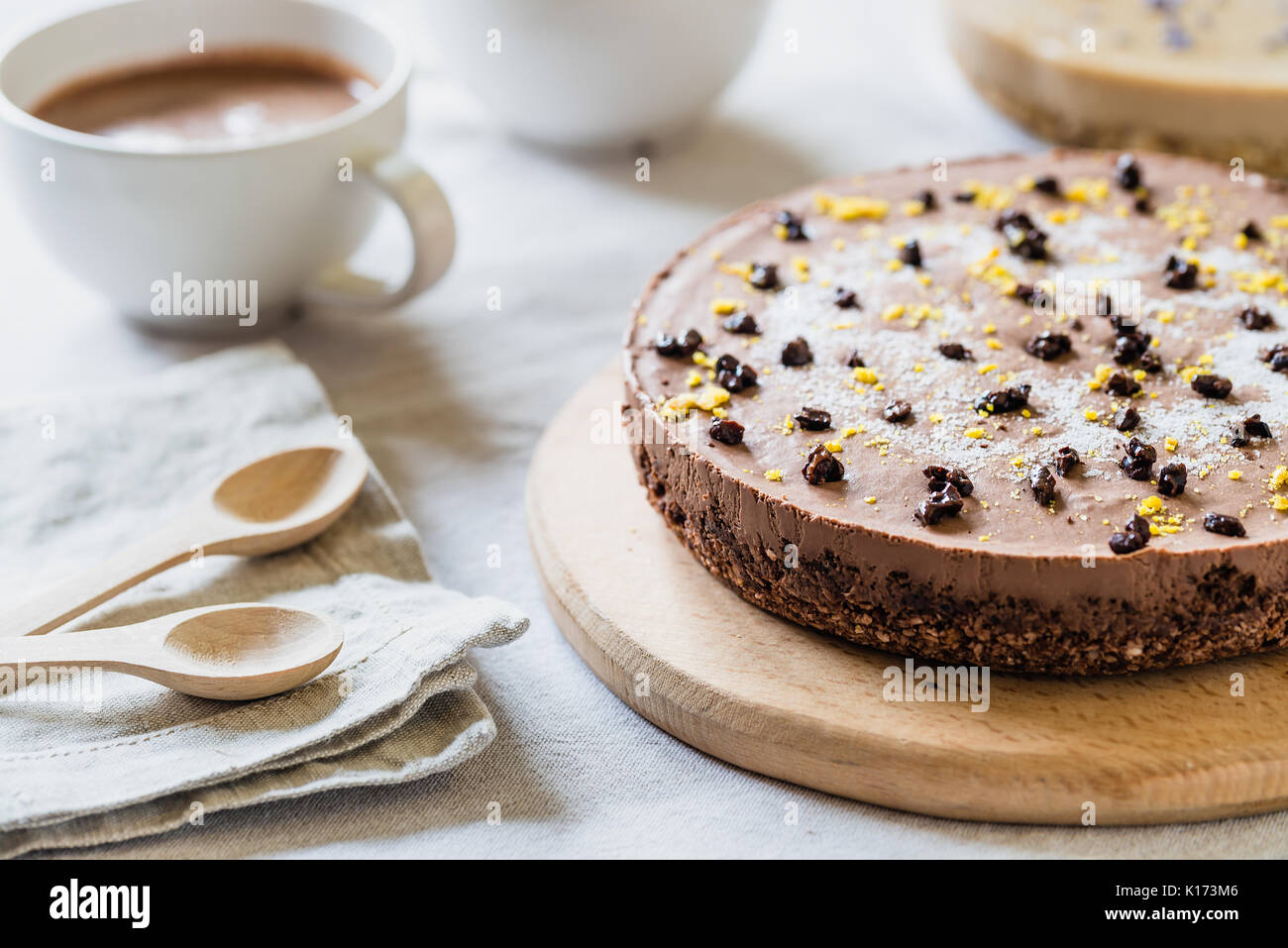 Raw healthy cheesecake, homemade with vegan chocolate. Breakfast table with hot drink - Stock Image
