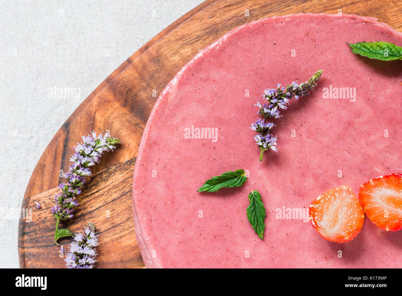 Raw healthy cheesecake, homemade with mint and strawberries. Top view, close up - Stock Image