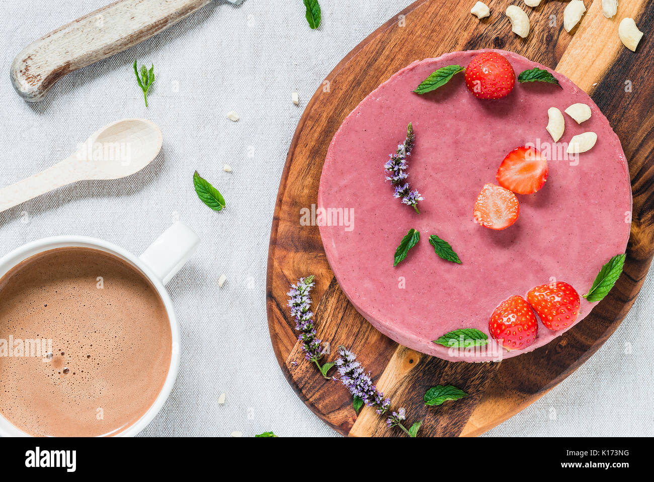 Raw healthy cheesecake, homemade with mint and strawberries. Breakfast table with hot drink. Top view - Stock Image