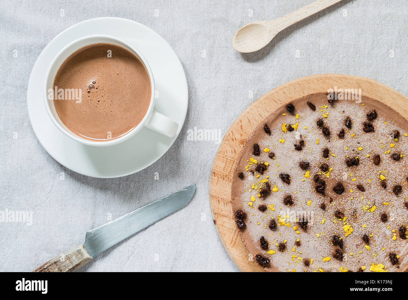 Raw healthy cheesecake, homemade with vegan chocolate. Breakfast table with hot drink. Top view Stock Photo