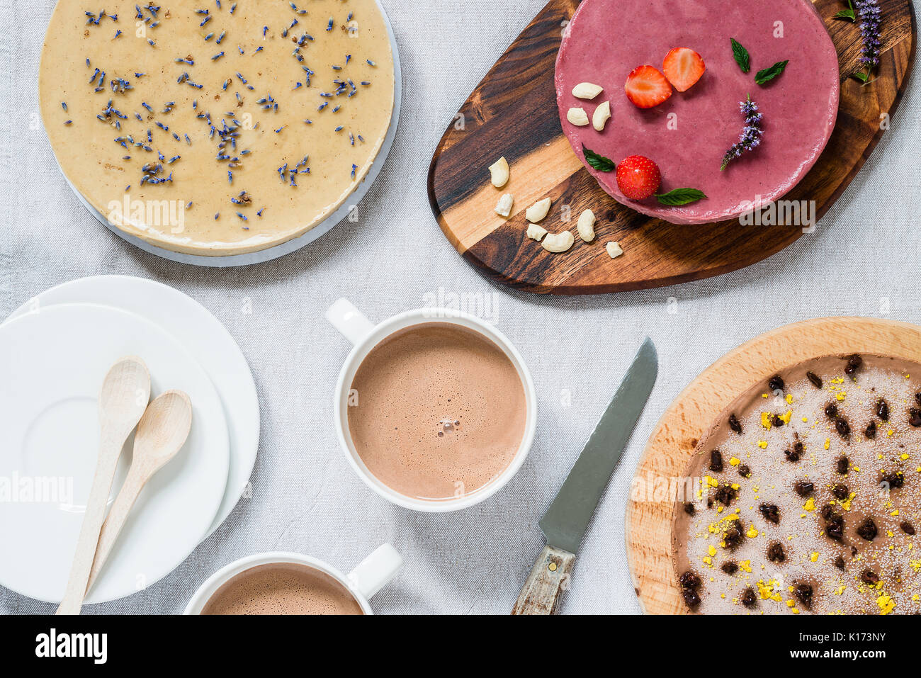 Different raw healthy cheesecakes, homemade with lavender, mint and strawberries. Breakfast table with hot drink. Top view - Stock Image