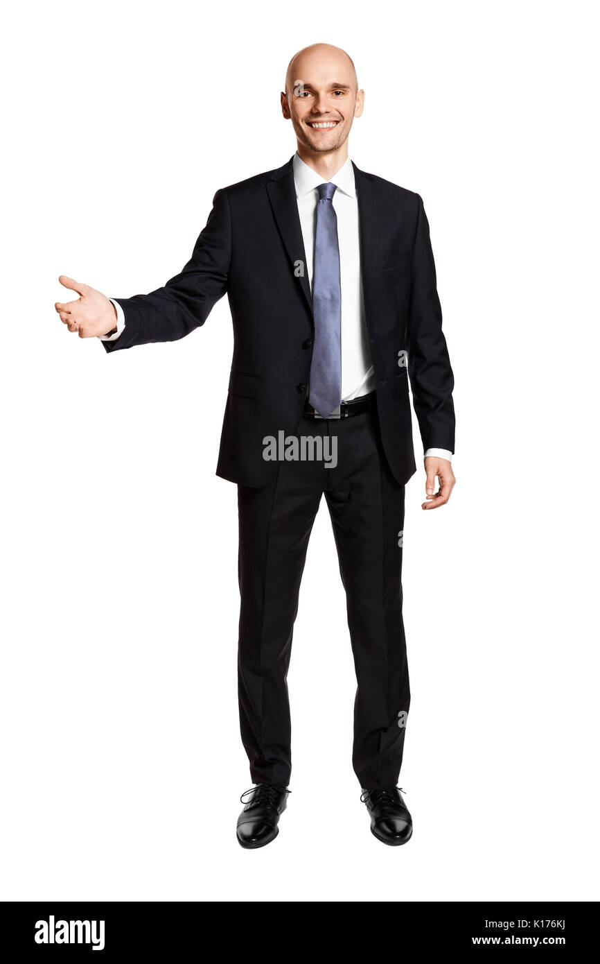 Young businessman greets his guests. Portrait of man in suit isolated on white background. - Stock Image