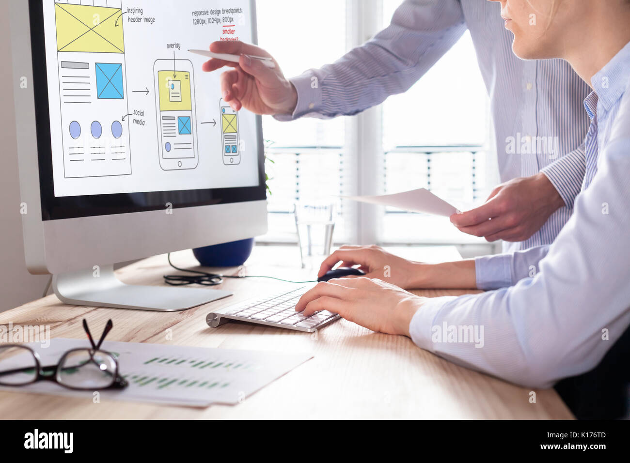 Website development team sketching wireframe layout design for responsive web content, two UI/UX front end designers in office - Stock Image