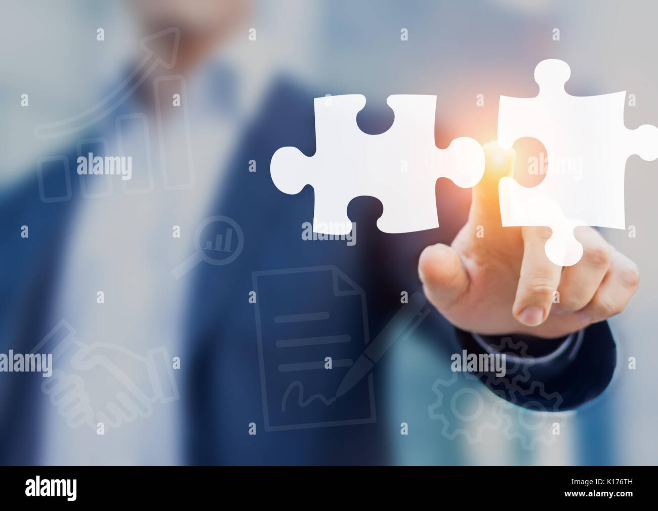 Mergers and acquisition concept with consultant touching icons of puzzle pieces representing the merging of two companies or joint venture, partnershi - Stock Image