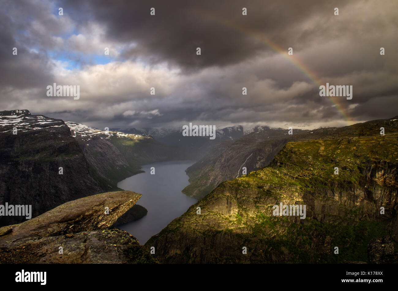 Rainbow over Trolltunga in cloudy weather, Norway - Stock Image
