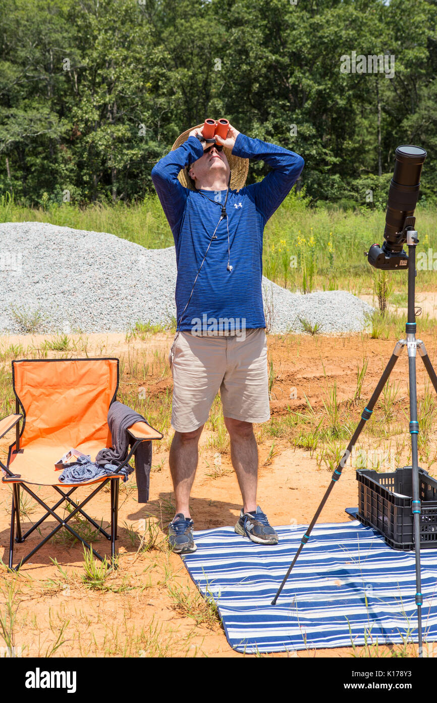 A photographer with solar binoculars observes the Great American Eclipse on August 21, 2017. - Stock Image