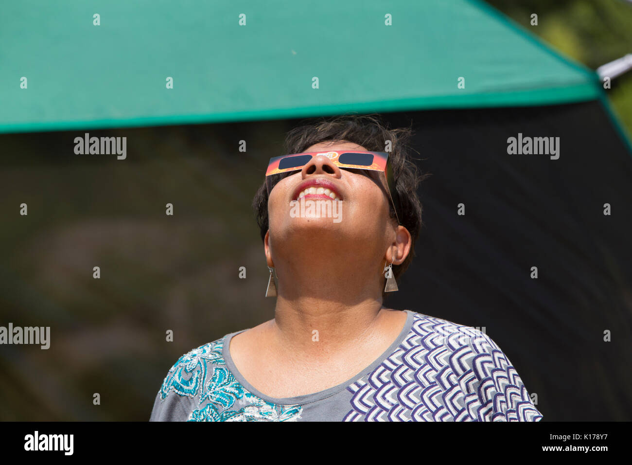 A woman wearing eclipse glasses observes the Great American Eclipse on August 21, 2017. - Stock Image