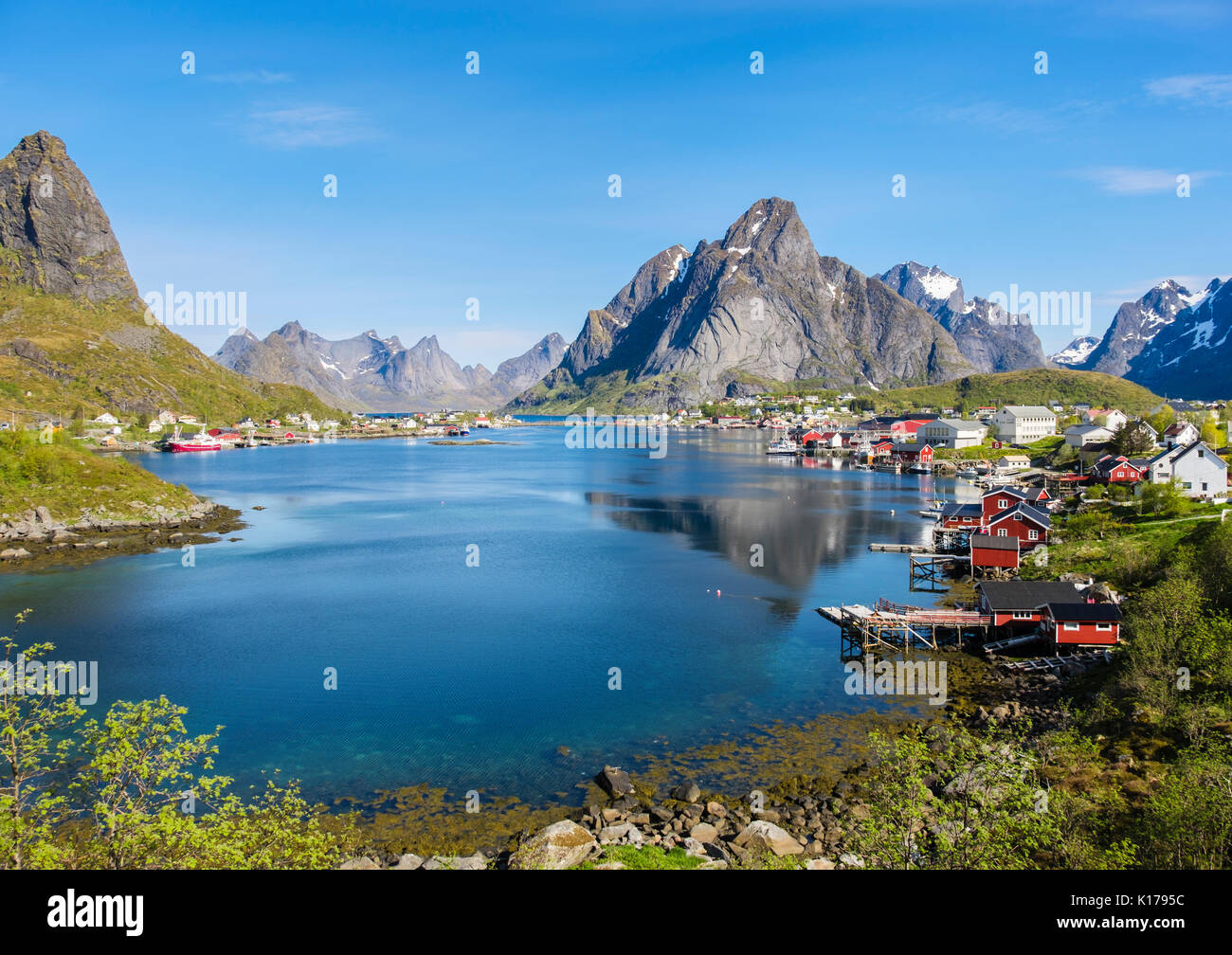 Scenic view across natural fishing harbour to mountains in summer. Reine, Moskenes, Moskenesøya, Lofoten Islands, Nordland, Norway - Stock Image