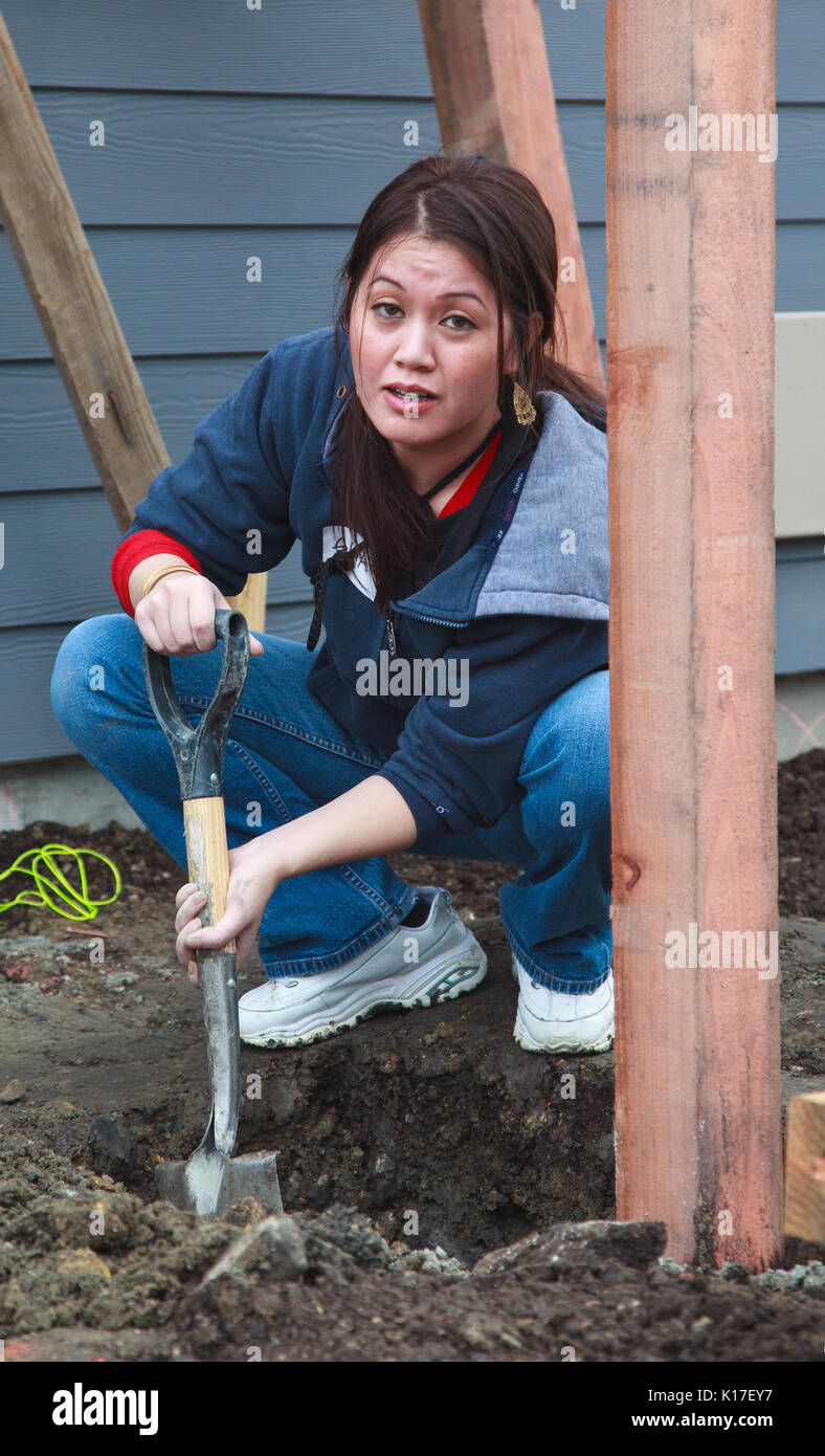 Woman digs post hole for Habitat For Humanity, Kinsell Commons, Oakland, Calif, Dec 3, 2010 - Stock Image