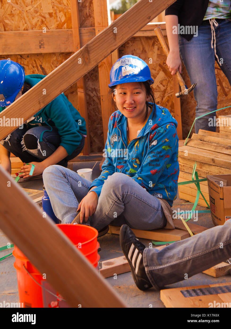 Woman talks while working for Habitat For Humanity. El Rincon, Oakland, Calif on Jan 22, 2011 - Stock Image