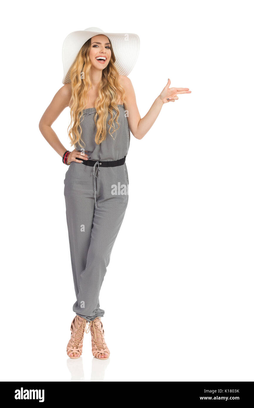 Happy beautiful young woman in dotted jumpsuit, white sun hat and high heels is standing with legs crossed, looking at camera, pointing with two finge - Stock Image