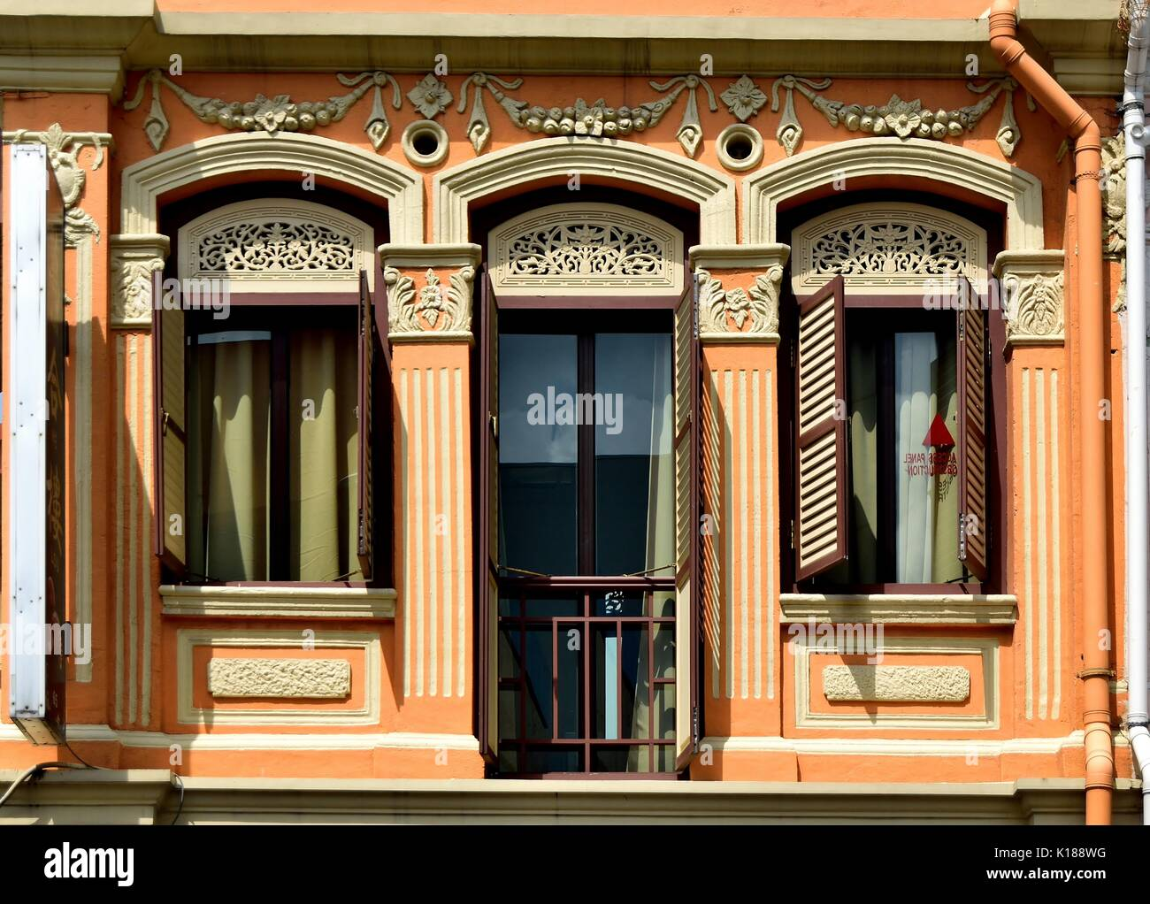 Traditional Shop House Exterior With Wooden Louvered Shutters, Peach Facade  And Fluted Corinthian Columns In The Little India District Of Singapore