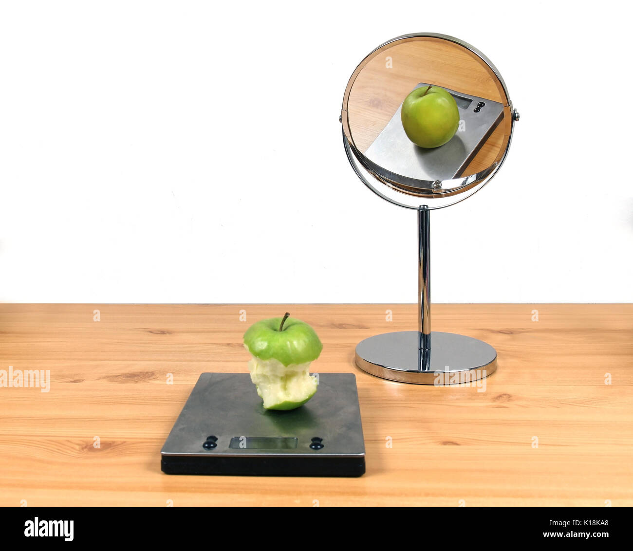 Concept about body image distortion with eaten apple and fat apple in the mirror - Stock Image