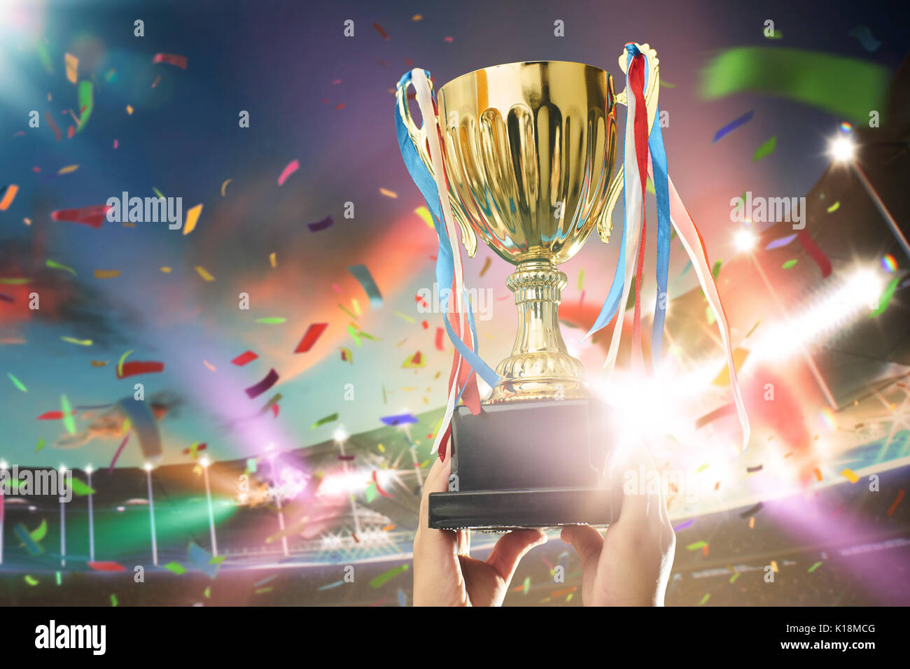 Young athlete holding up a gold trophy cup with space ready for your trophy design. Grand stadium celebration with spotlight , flare and confetti .. - Stock Image
