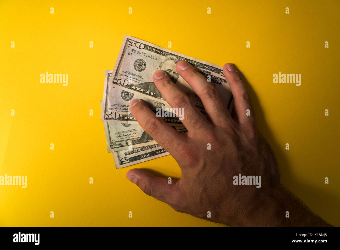 The man's hand covered the dollars banknotes. Protecting your money. Lack of money. Dollars banknotes closeup. Stock Photo