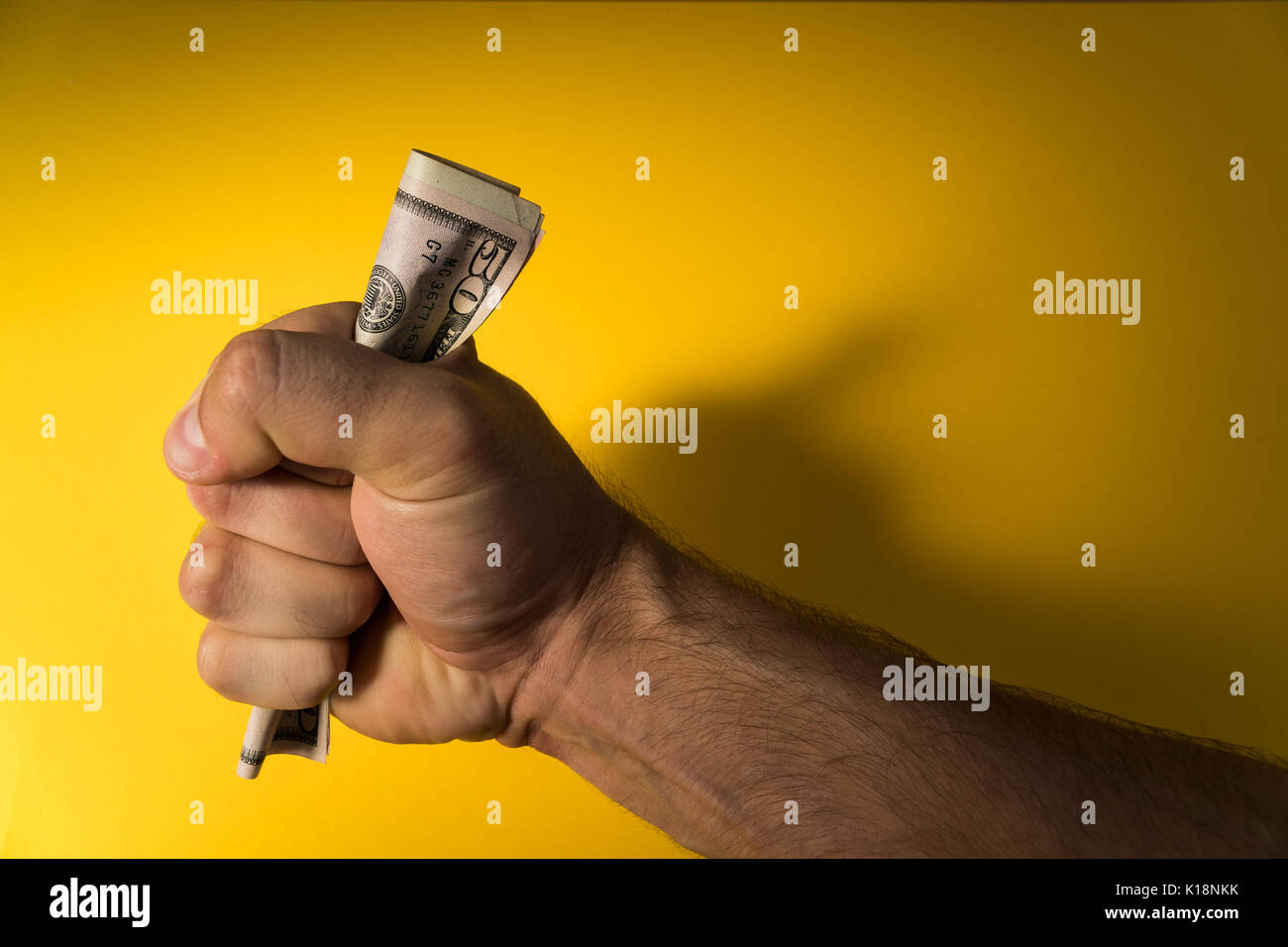A man's hand holds out dollars. Hand and money on a yellow background. Lack of money. Family budget. Stock Photo