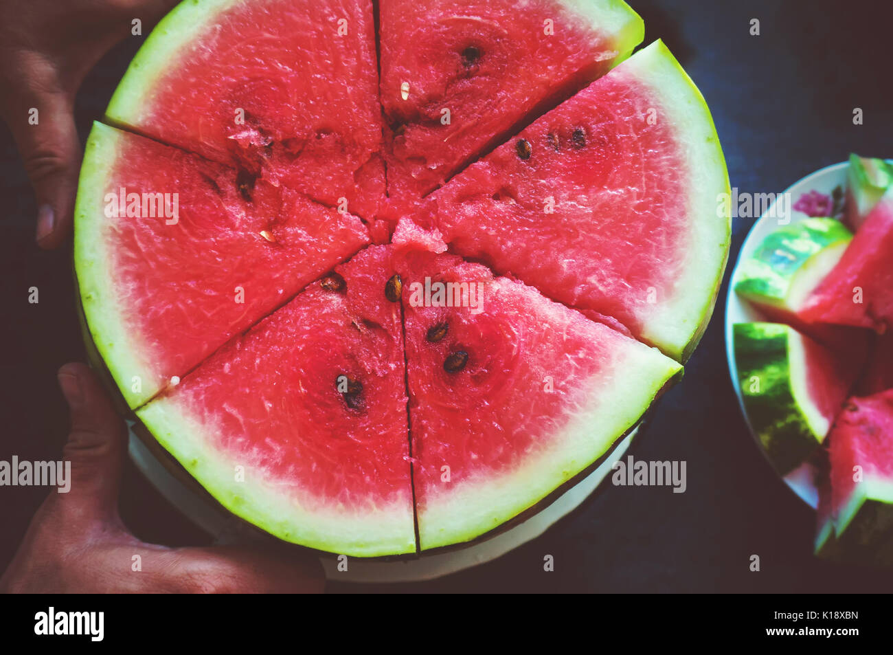 A man cuts a ripe red watermelon. Slices of watermelon closeup - Stock Image