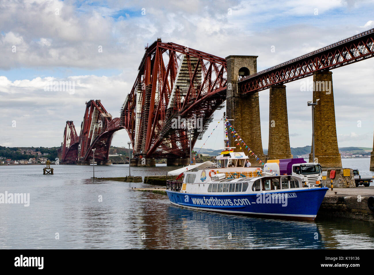 The iconic Forth Rail cantilever bridge viewed from the South Queensferry promenade with Maid of the Forth ferry with passengers for Inchcolm - Stock Image