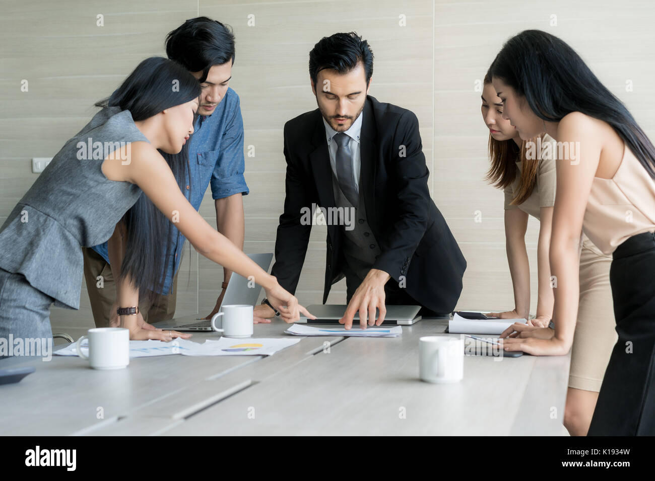 Group of multi-ethnic business partners discussing ideas in meeting room at office. Business people meeting corporate communication teamwork concept. - Stock Image