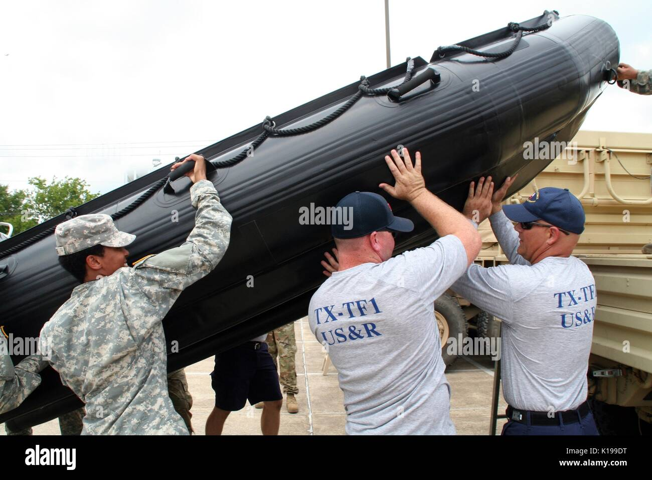 U.S. Texas Army National Guard soldiers joined members of a Texas Task Force One Swift Water Rescue Team loading a Zodiac boat in preparation for Hurricane Harvey August 25, 2017 in Bryan, Texas. Hurricane Harvey is now a category 4 storm expected to hit the Texas coast causing major damage and flooding. - Stock Image