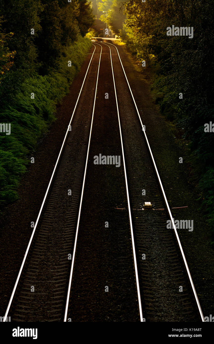 UK rail line tracks with no train on early morning as the sun rise begins to illuminate the tracks with a warm glow from the sun, Delamere, Cheshire, UK - Stock Image