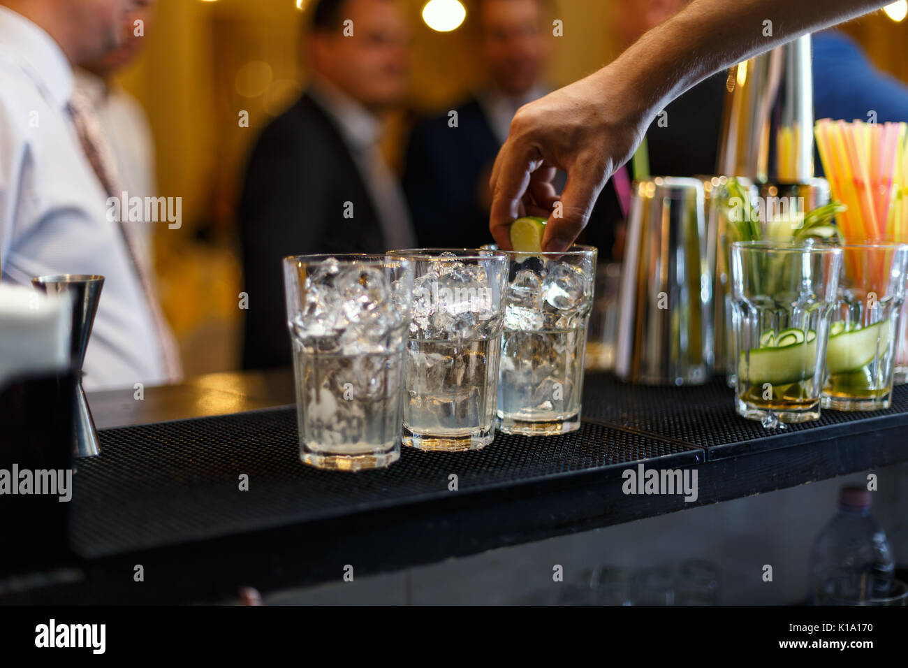 Bartender muddling lime to make a cocktail - Stock Image
