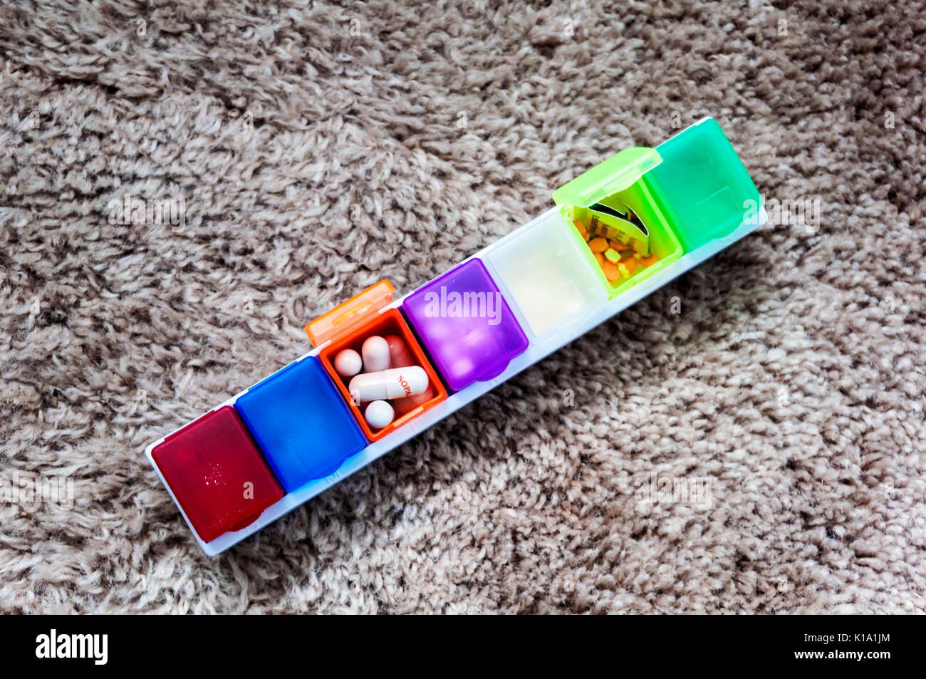 Pill box with compartments in many colours - Stock Image