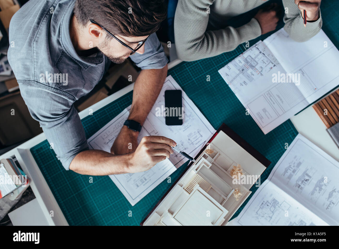 Top view of two male architects sitting in office and working on project. Creative people working on new architectural Stock Photo