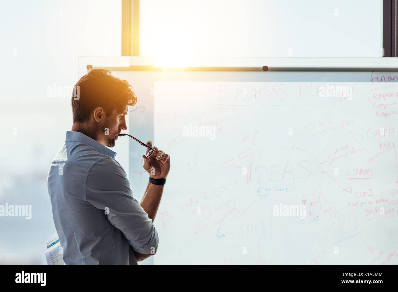 Business investor in deep thought looking at the business ideas written on the whiteboard. Businessman thinking while holding his spectacles to mouth - Stock Image