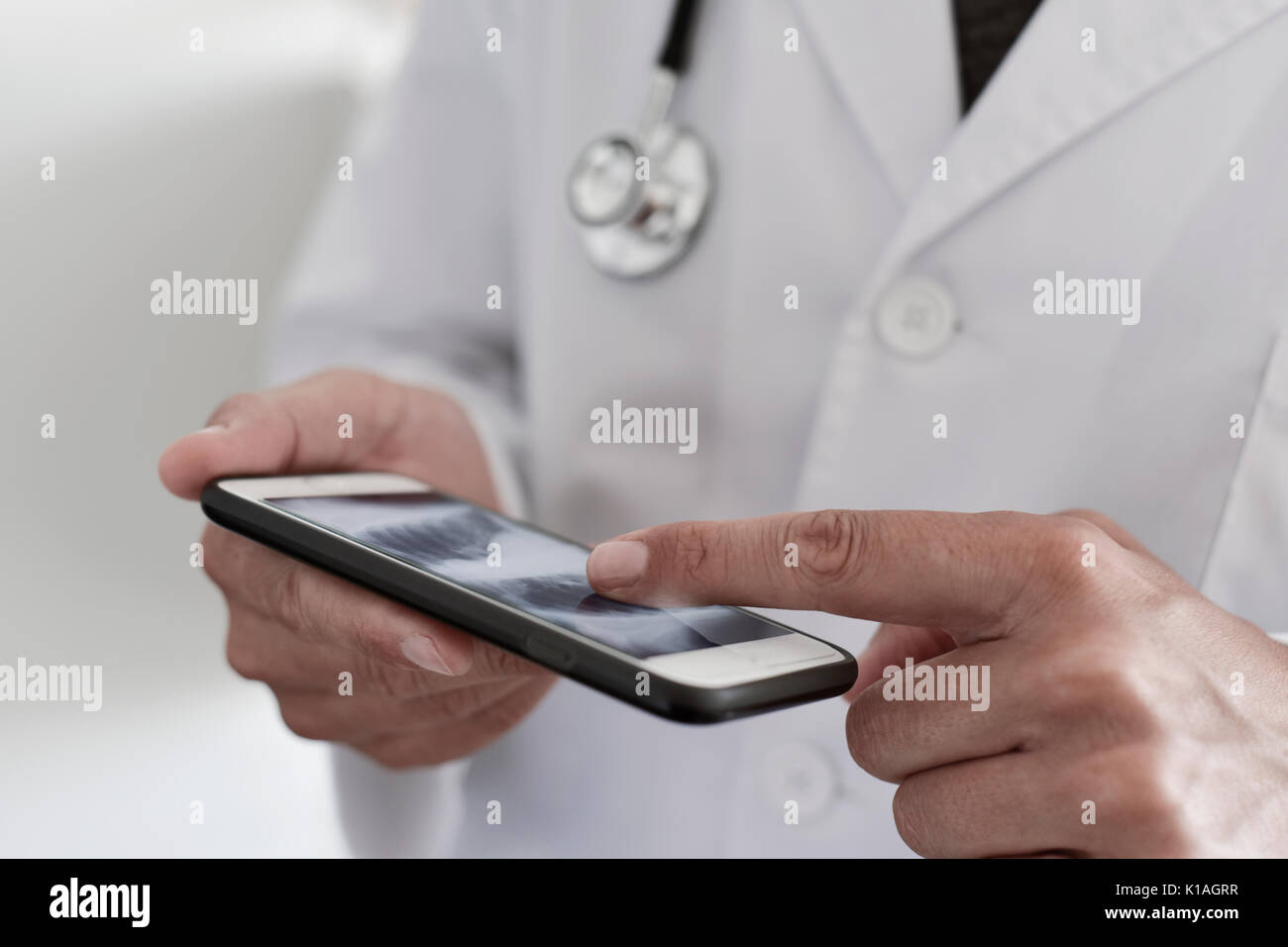 closeup of a young caucasian doctor man wearing a white coat checking a chest radiograph in a smartphone - Stock Image