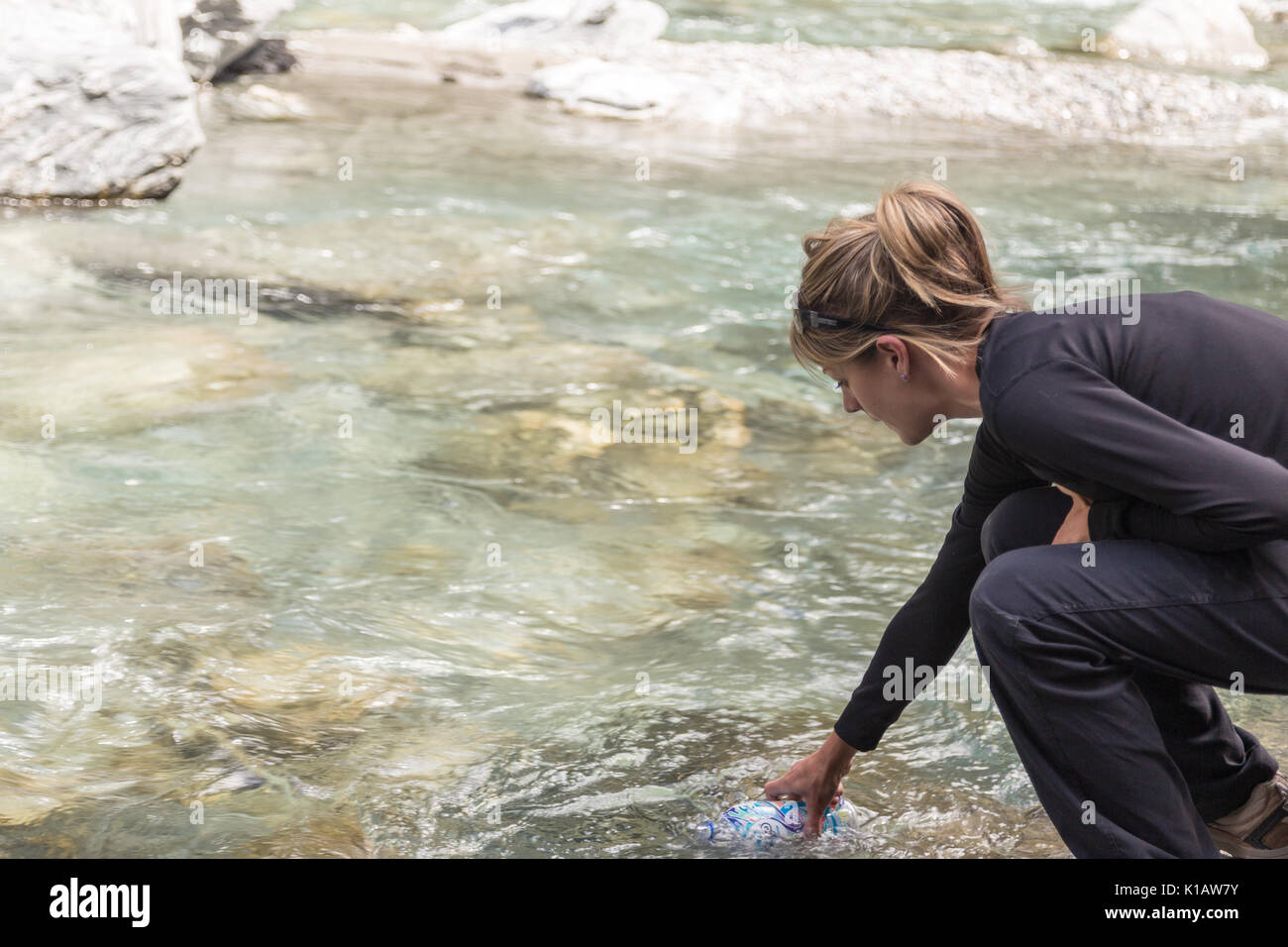 A woman or girl fills a water bottle from a crystal clear river or stream in New Zealand - Stock Image