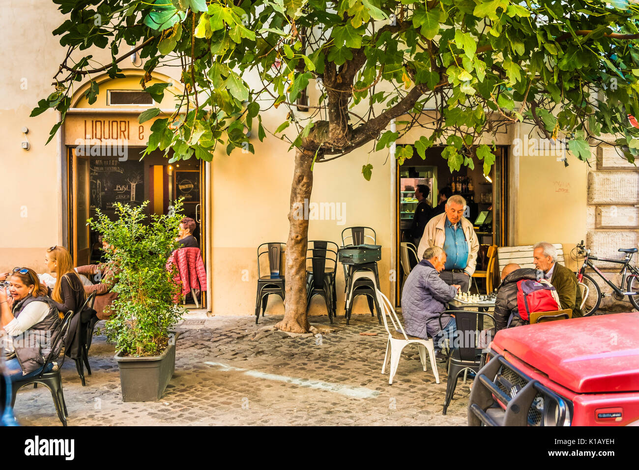 street scene, old men playing chess at a sidewalk cafe in the historic city center of rome - Stock Image